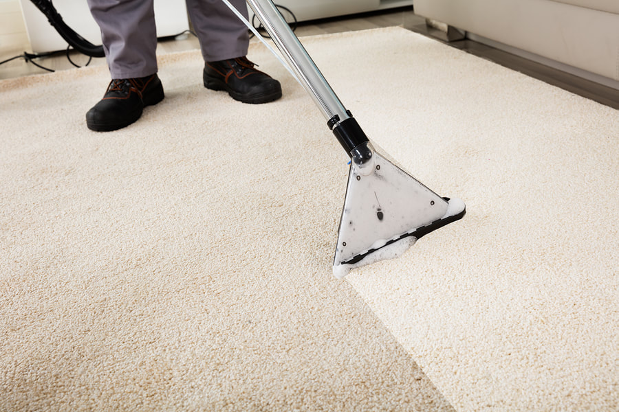 man cleans the carpet with a machine